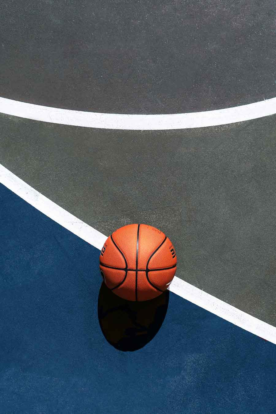 Basketboll på en basketplan. bakgrund delvis färgad i mediehusets färger