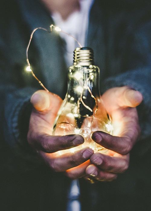 Glödlampa med lysande tråd i händerna på kostymklädd person